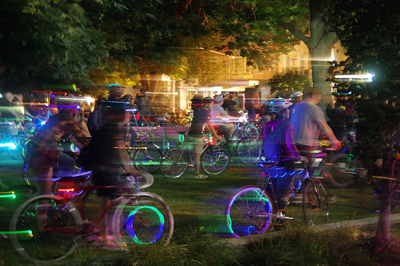 colour photo of people on bikes at night in a park